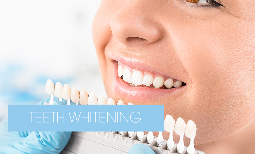 dentist checking tooth colour after teeth whitening